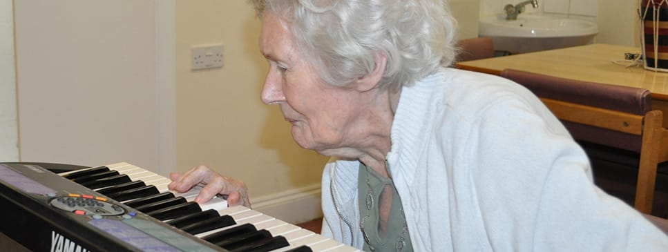 resident living with dementia playing a keyboard