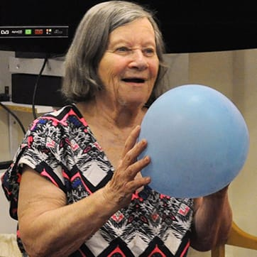 Resident enjoying movement to music activities with a balloon
