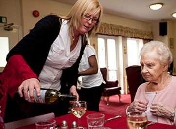 Pouring wine at the Devonshire Dementia Care home